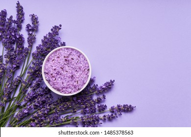 Lavender SPA. Lavender flowers and lavender bath salt in bowl on purple background. Copy space, top view. SPA concept.