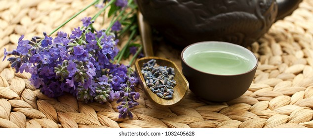 Lavender tea in a clay teapot, cup and scoopp of dry blossoms, fresh lavender flowers on a table in the garden