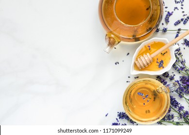 lavender tea in a cup and teapot with honey and fresh flowers over white marble table. herbal drink. top view with copy space