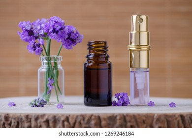 lavender water and essential oil bottle and fresh lavender flowers for relax on brown background