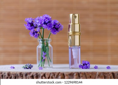 lavender water in glass bottles and fresh lavender flowers for relax on brown background