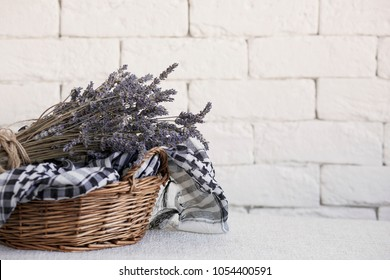 Lavender in a wicker basket against a white brick wall. Shabby chic interior decor for farmhouse. Provence home decoration.