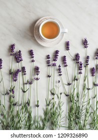 Lavenders and white cup of lavender tea on white table. Overhead shot.