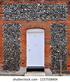 LAVENHAM, SUFFOLK, UK - AUGUST 4, 2018. Flint stonework surrounds the entrance to an ancient house, appropriately named Flint Cottage, located at Lavenham, in the English county of Suffolk, UK.
