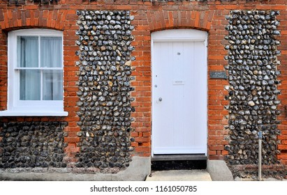 LAVENHAM, SUFFOLK, UK - AUGUST 4, 2018. Flint stonework surrounds the entrance to Flint Cottage, an ancient dwelling located at Lavenham, in the English county of Suffolk, UK.