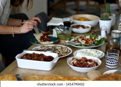 Lavish homemade lunch served on table: focaccia bread, prosciutto, porchetta, mozzarella cheese, pesto, caponata, caramelized onion, with arugula and cherry tomato salad. Selective focus.