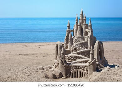 A lavish and large sand castle on an empty beach.