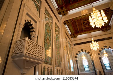 Lavishly decorated interior of the Sultan Qaboos Grand Mosque in Muscat, Oman, showing the main pulpit.