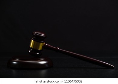Law or auction gavel on a wooden office desk. Closeup front view with details, space for text, blur background