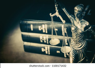 Law books and Scales of justice on a desk