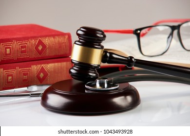 Law books with wooden judges gavel and medical stethoscope on white table in a courtroom or enforcement office, close-up. Medicine law concept.