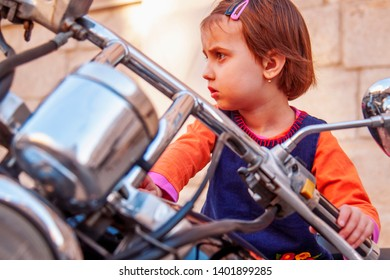 Law for child drivers under 18 concept. Portrait of cute little biker child girl sitting on a motorcycle.
