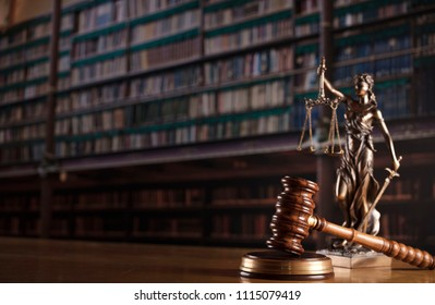 Law concept. Judge's gavel, statue and scales of justice. Old courtroom library. Wooden desk.