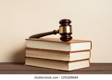 Law concept. Judge gavel on stack of law books on table in a courtroom .