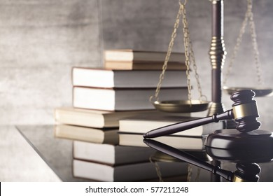 Law concept. Mallet of the judge, books, scales of justice. Gray stone background, reflections on the floor, place for typography. Courtroom theme.
