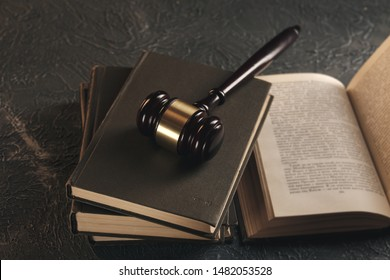 Law concept - Open law book with a wooden judges gavel on table in a courtroom or law enforcement office on blue background.