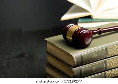 Law concept - Open law book with a wooden judges gavel on table in a courtroom or law enforcement office isolated on white background. Copy space for text