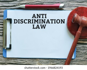 Law concept. Phrase anti discrimination law written on paper clipboard with a pen and gavel.