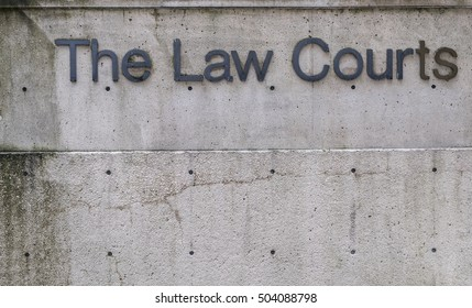 The Law Courts sign on a concrete wall outside a courthouse.
