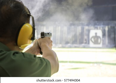 law enforcement aiming and shooting gun in academy shooting range surround with smoke and copy space