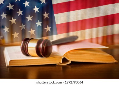 Law enforcement and the judiciary in the United States with a composite image of a judges gavel on a law book in the courtroom against the Stars and Stripes national flag
