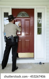Law enforcement officer posting an eviction notice