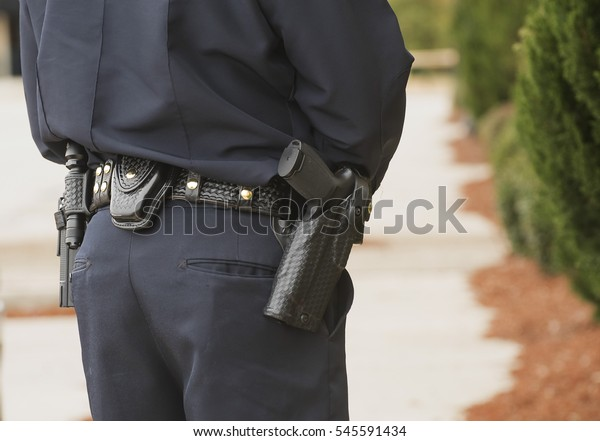A law enforcement officer wears a duty belt, carrying a pistol, handcuffs, a collapsible baton and a two-way radio. Out of view in this photo are ammunition and pepper spray.