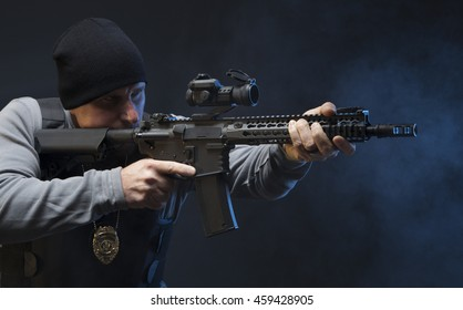 Law Enforcement Special Agent with weapon, sighting in on the target.