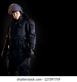 Law enforcer in protective uniform ready for crowd control isolated on black