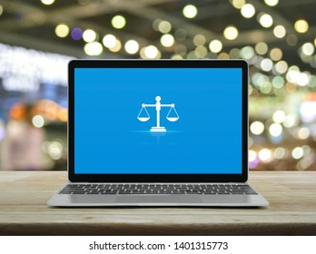 Law flat icon with modern laptop computer on wooden table over blur light and shadow of shopping mall, Business legal service online concept