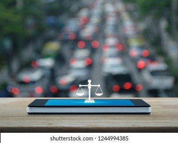 Law flat icon on modern smart mobile phone screen on wooden table over blur of rush hour with cars and road in city, Business legal service online concept