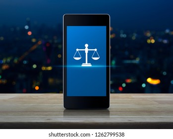 Law flat icon on modern smart mobile phone screen on wooden table over blur colorful night light of city tower and skyscraper, Business legal service online concept