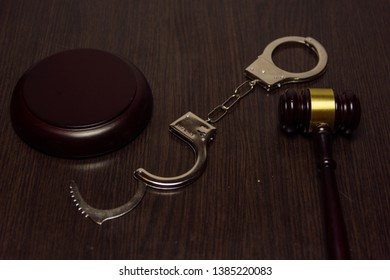 Law and gustice. Hammer of a judge and handcuffs on a wooden background