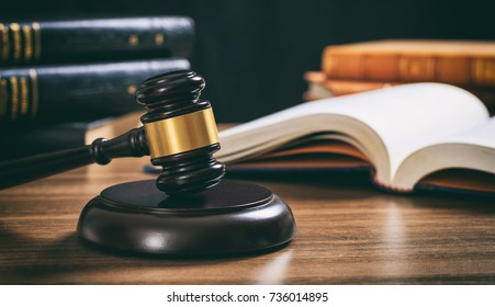 Law judge gavel on a wooden desk, blur legal books background