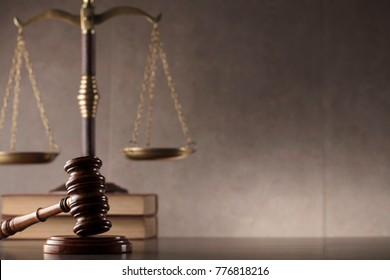 Law and justice concept background. Gavel, scales of justice, books. Gray stone background, place for typography.