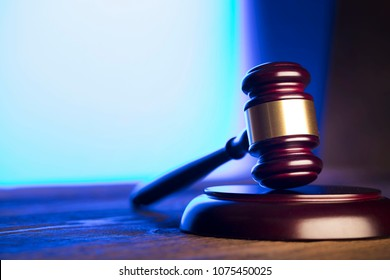 Law and justice concept. Gavel, wooden table, blue light.