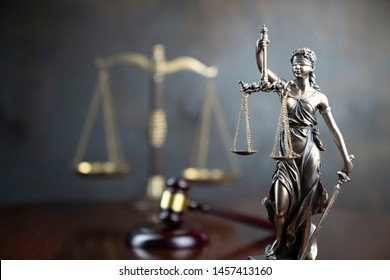 Law and justice concept. Lawyers desk. Judge's gavel, statue of justice, scales, wooden table. Gray bokeh background.