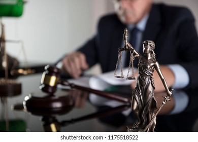 Law and justice concept. Male judge on gray background, statue of justice, gavel, bokeh.