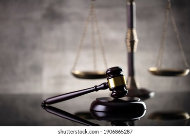 Law and justice concept. Mallet of the judge, hourglass, scales of justice. Gray stone background, reflections on the floor. Place for typography. - Shutterstock ID 1906865287