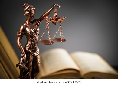 Law and Justice concept. Mallet of the judge, books, scales of justice. Gray stone background, reflections on the floor, place for typography. Courtroom theme.