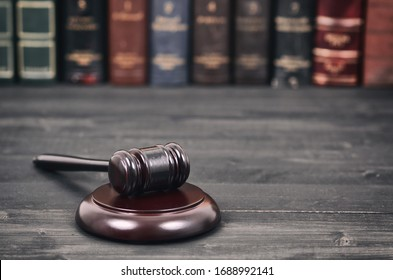 Law and Justice, Legality concept, Judge Gavel on a black wooden background in front of a law library.