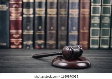 Recht und Gerechtigkeit, Legalität Konzept, Richter Gavel auf schwarzem Holzhintergrund vor einer Gesetzesbibliothek.