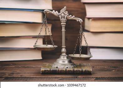 Law and Justice, Legality concept, Scales of Justice and law books on a wooden background.