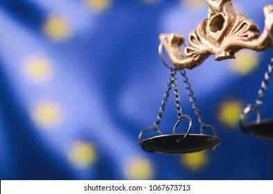 Recht und Gerechtigkeit, Legalitätsbegriff, Justizskala, Justitien, Dame Justice vor der Flagge der Europäischen Union im Hintergrund.