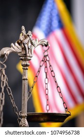 Law and Justice, Legality concept, Scales of Justice in front of the American flag in the background.