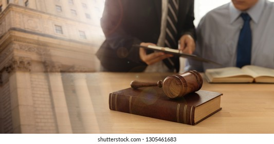 Law and Legal advisor concept. judges gavel on law books and lawyer meeting with client at law firm and court.