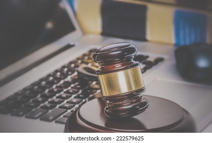 Law legal concept photo of gavel on computer with legal books in background.