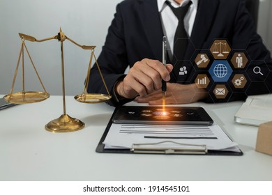 Law and Legal services concept, Lawyer man working with digital tablet  at the table office and law technology interface icons, Blurred background.