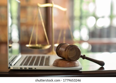 law legal technology concept.  judge gavel on computer with scales of justice on desk of lawyer.