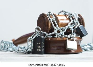 Law and legislation obstruction concept with judge wooden hammer or gavel surrounded by chains and locks